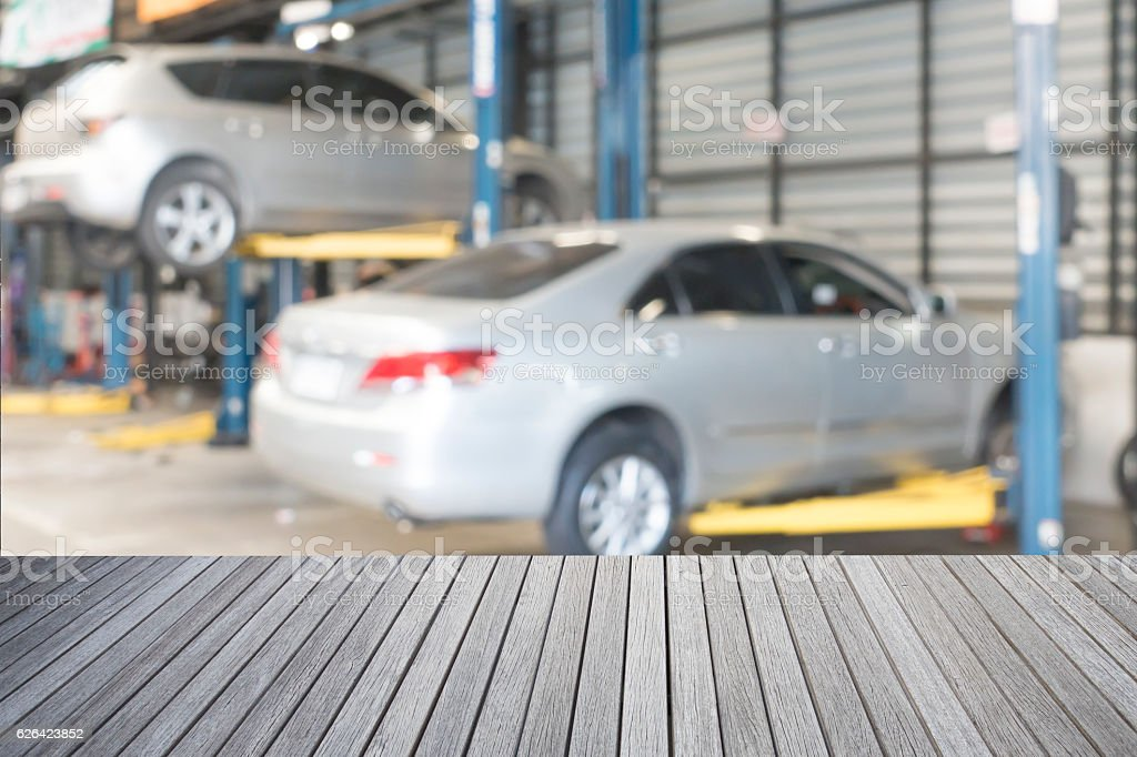 Empty top wooden table and blurred car technician repairing the stock photo