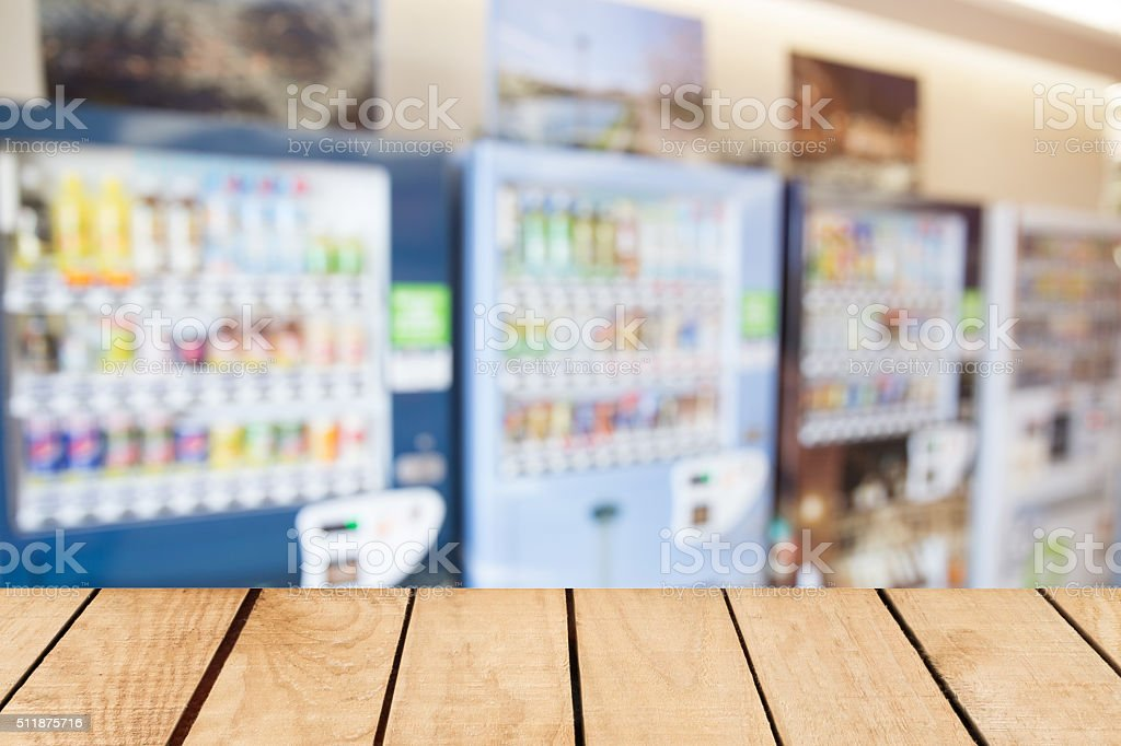 Empty top wooden table and blurred image of vending machine stock photo