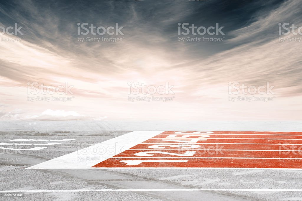 Empty track finish line against dramatic cloudy sky stock photo