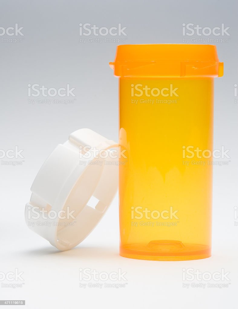 Empty, uncapped orange pill bottle, no label and white lid royalty-free stock photo