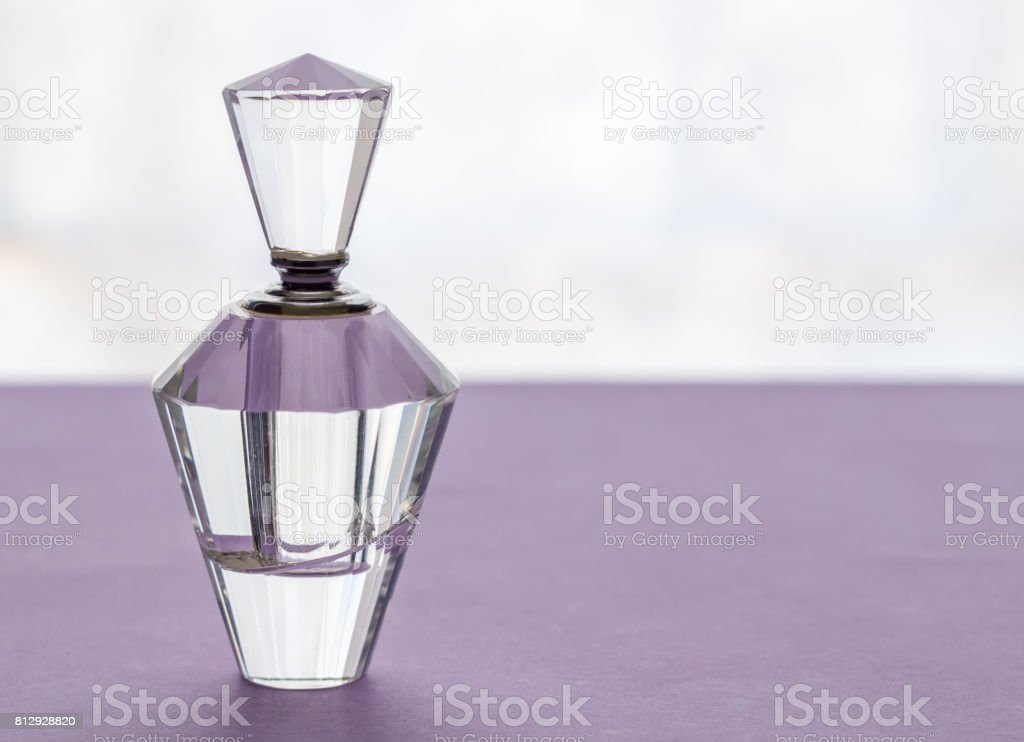 Empty vintage crystal glass perfume bottle with stopper on lilac background stock photo