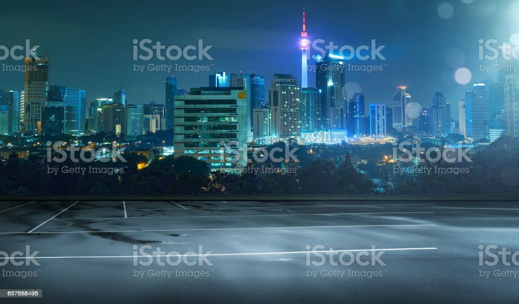Empty wet asphalt road and cityscape skyline at night with light flare bokeh effect . stock photo