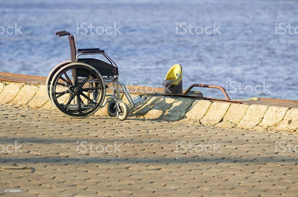 Empty wheelchair at harbor stock photo