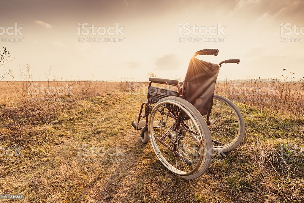 Empty wheelchair on the meadow at sunset - vintage version stock photo