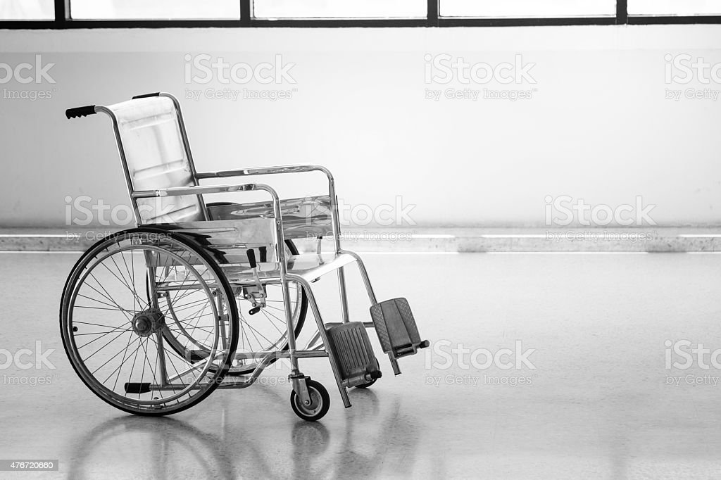 Empty wheelchair parked in hospital hallway stock photo