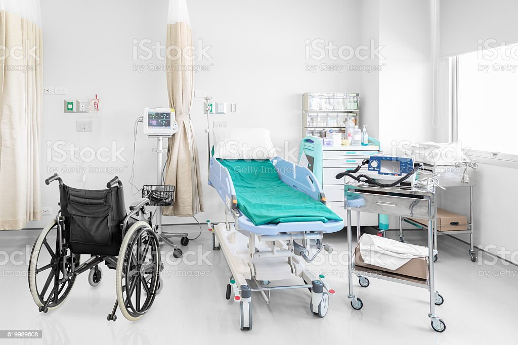 Empty wheelchair parked in hospital room stock photo