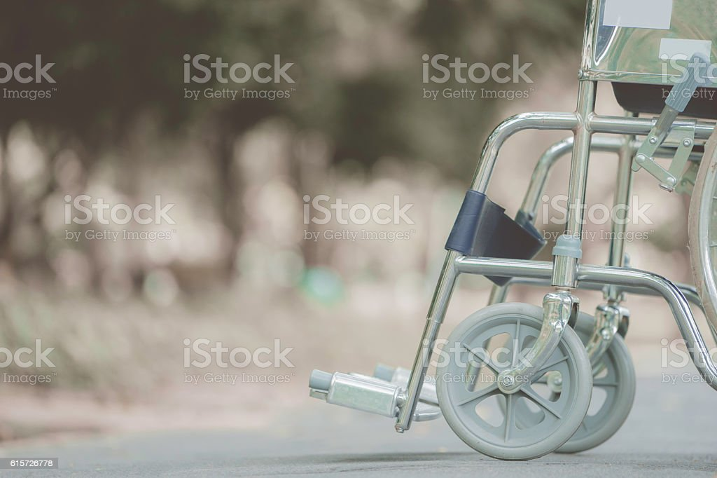 Empty wheelchair parked in park, retro filter effect stock photo
