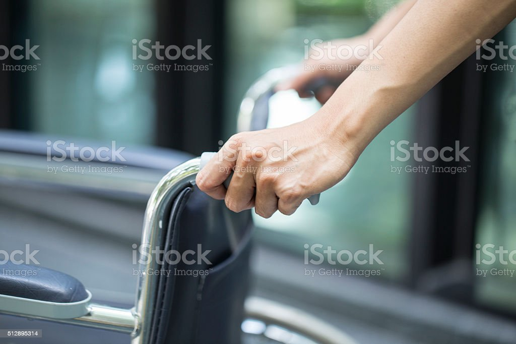 Empty wheelchair pushed by nurse's hands stock photo