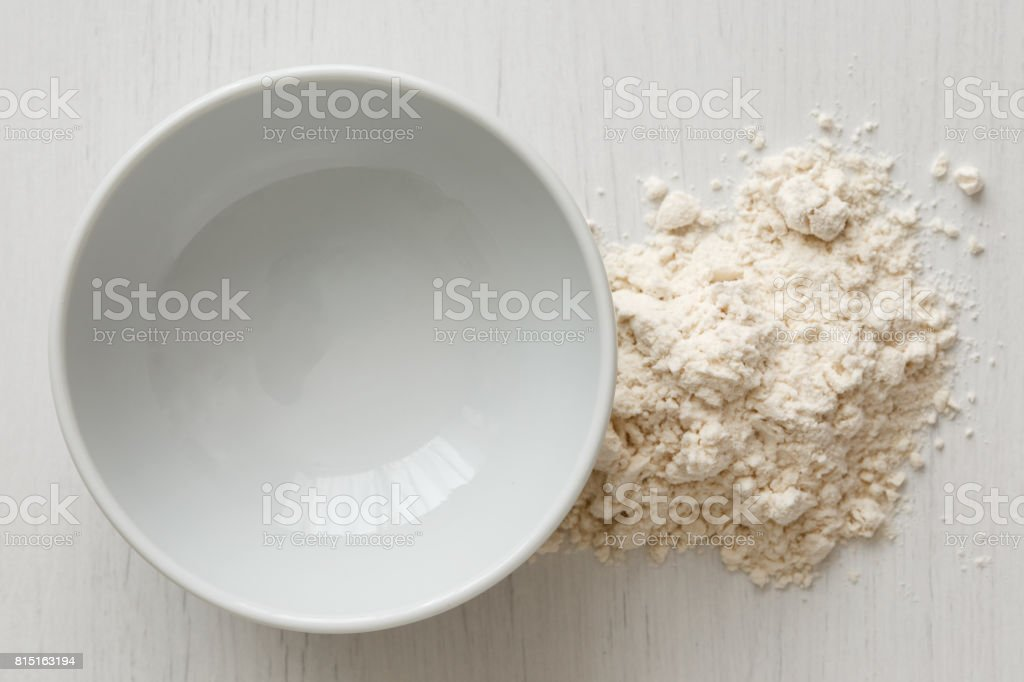 Empty white ceramic bowl isolated on white from above. Next to white flour. stock photo