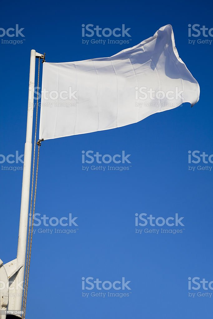 Empty white flag waves in front of deep blue sky stock photo
