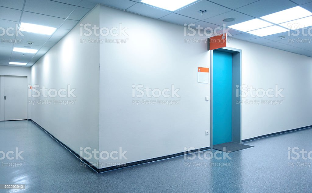 Empty white Hospital corridor with a blue door stock photo