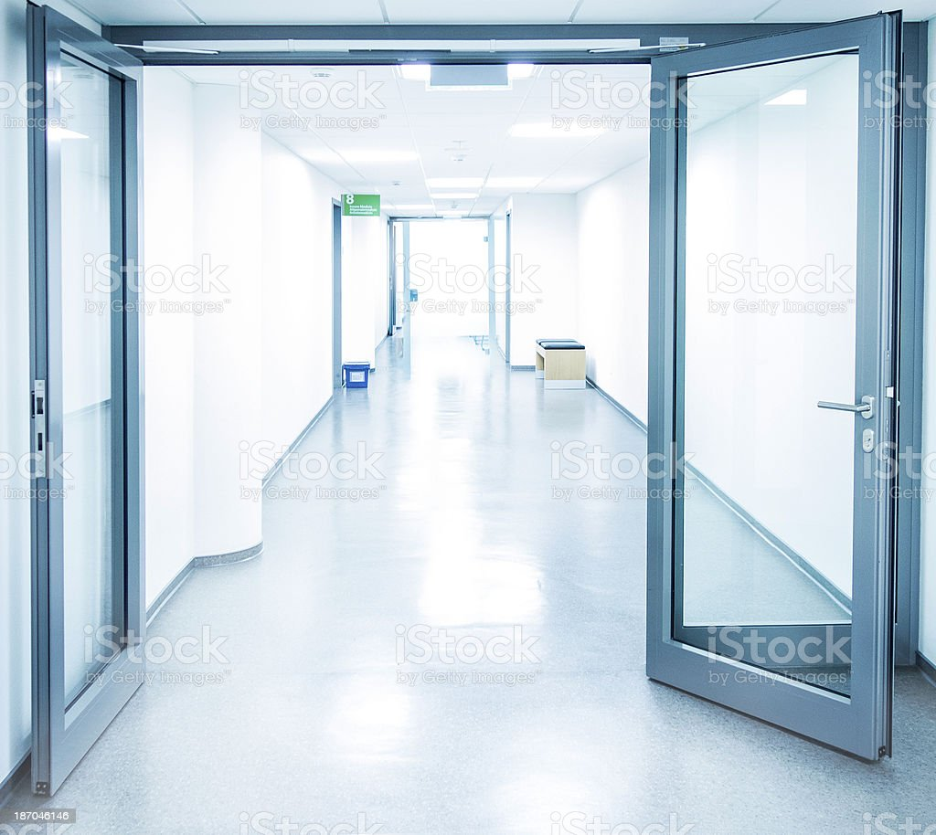 Empty white Hospital corridor with a blue open glass door stock photo