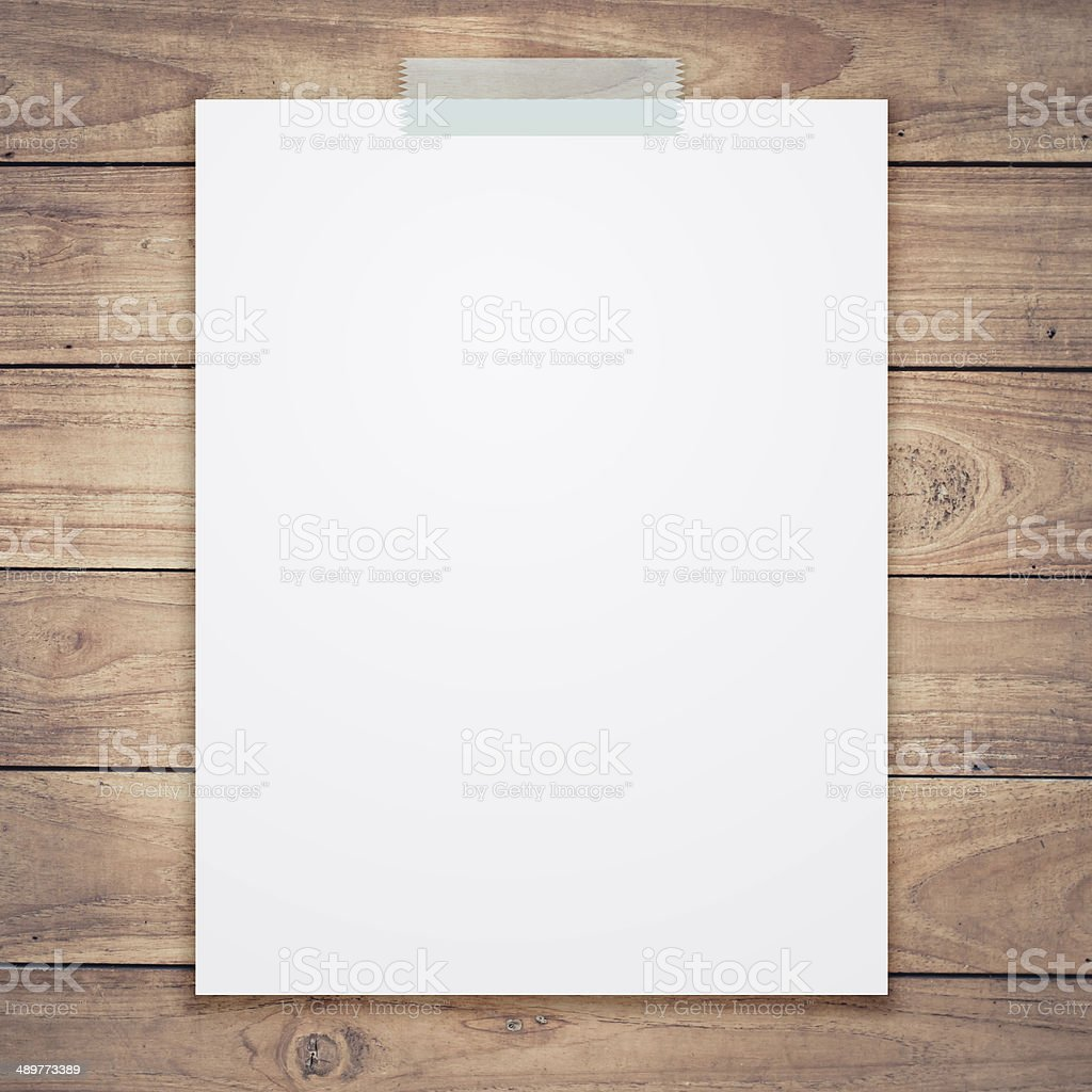 Empty white paper sheet stick on wood texture background. stock photo