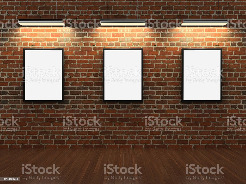 Empty white picture frames on a brick wall with lights above stock photo