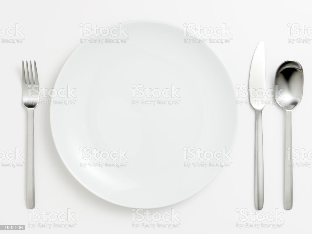 Empty white plate and fork spoon knife royalty-free stock photo