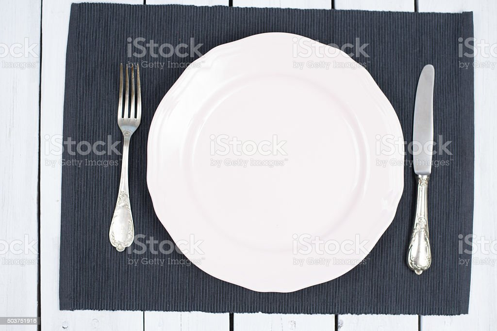 Empty white Plate on a black placemats with silverware stock photo