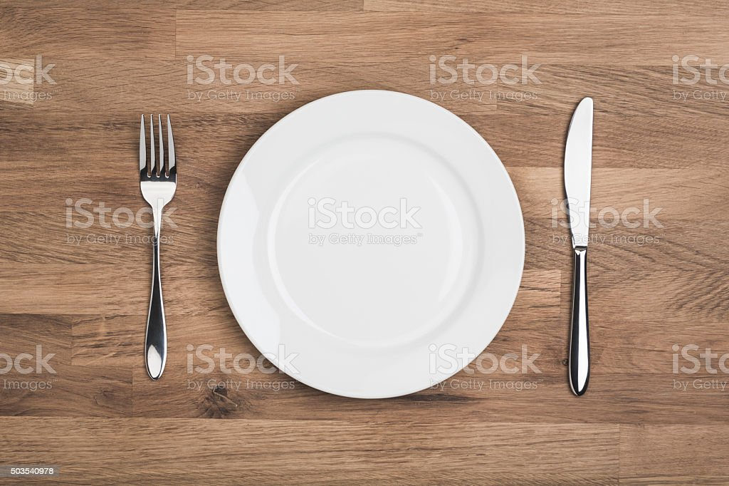 Empty white plate with knife and fork stock photo
