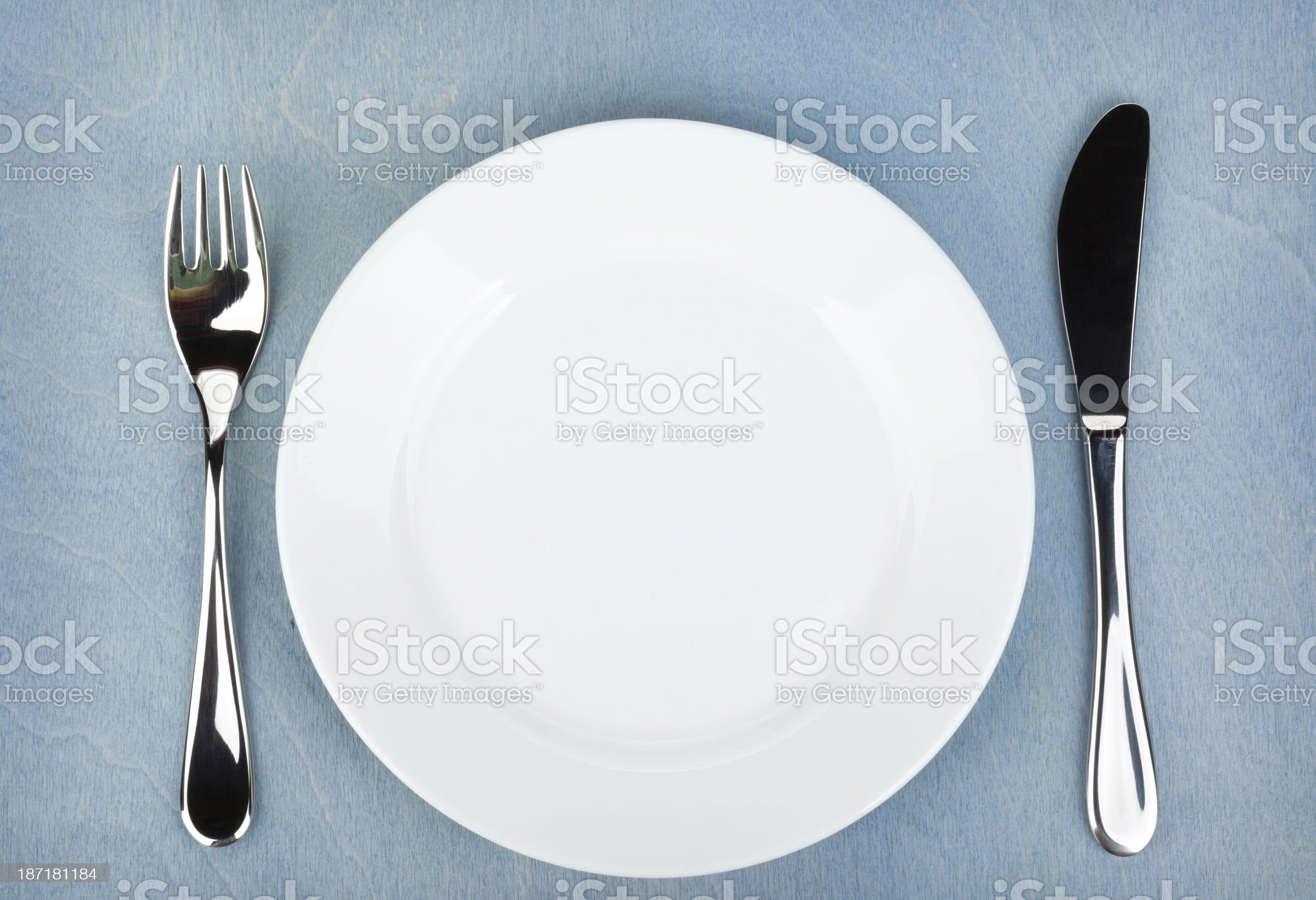 Empty white plate with silverware on wooden table royalty-free stock photo