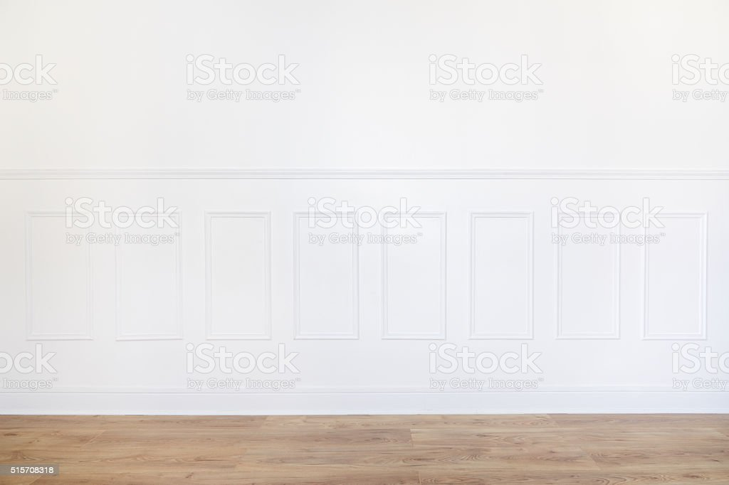 Empty white room with parquet floor and wood trimmed wall stock photo