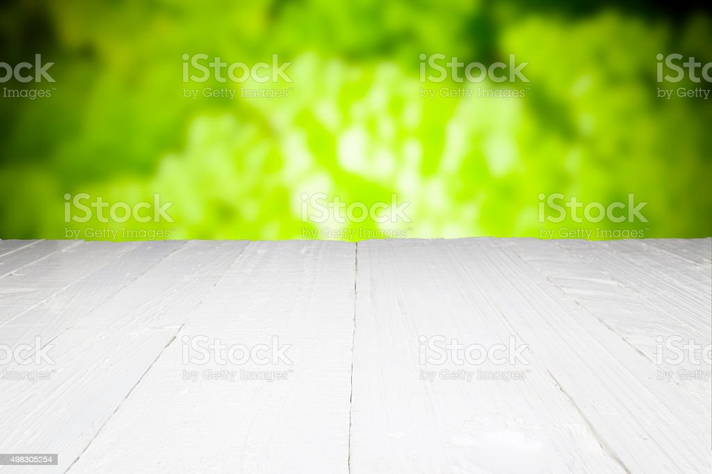 Empty white table with defocused green foliage at background stock photo