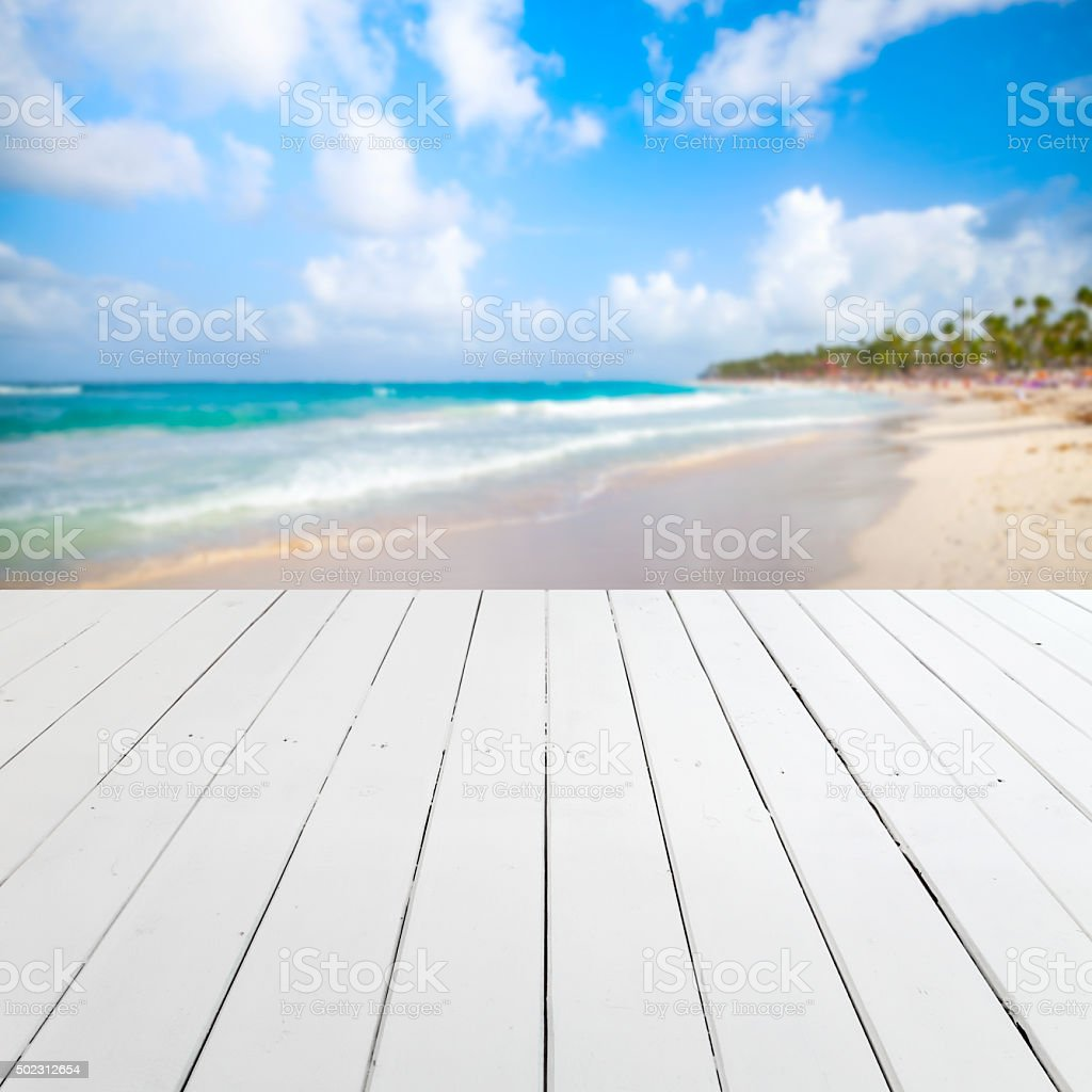 Empty white wooden pier with blurred beach stock photo