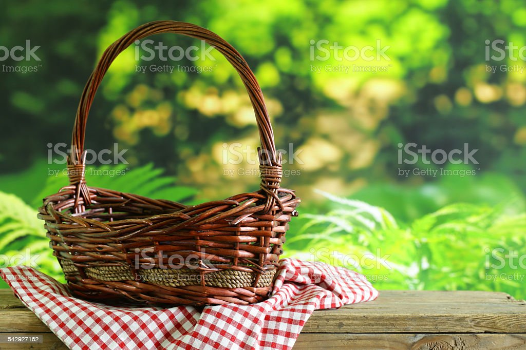 empty wicker basket and checkered plaid for picnic stock photo