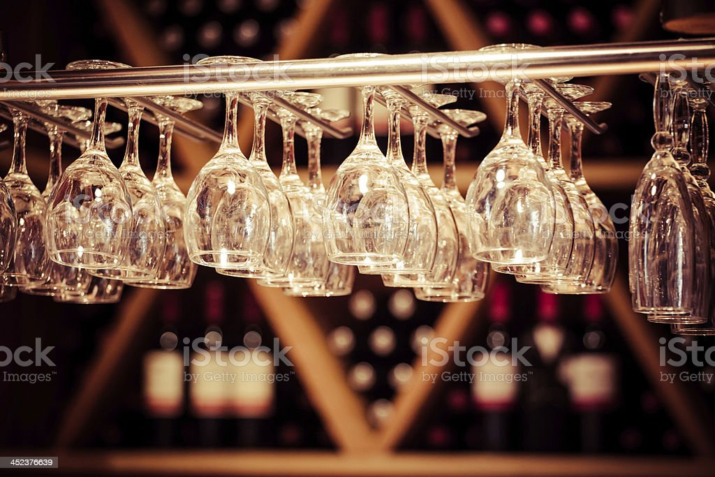 Empty wine glasses hanging with background wine display stock photo