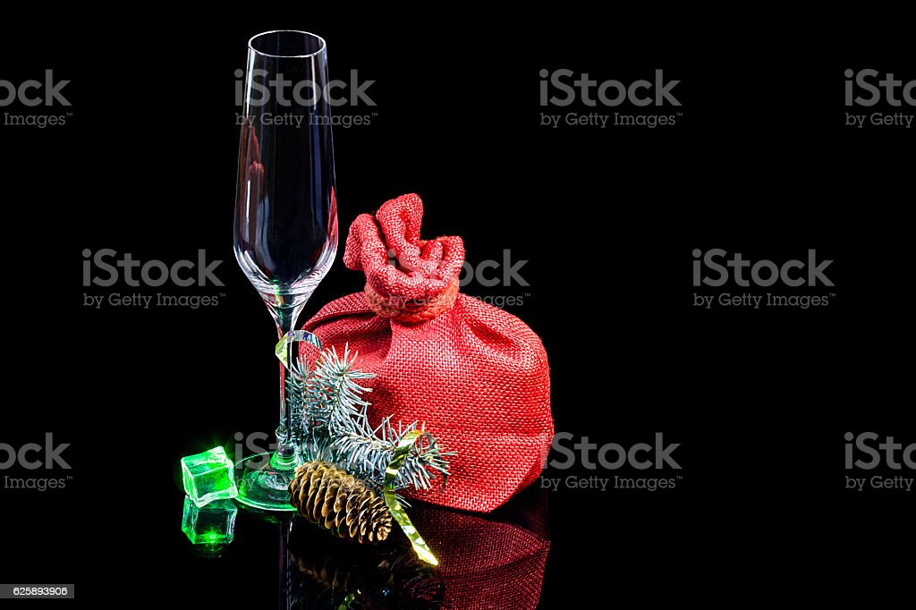 Empty wineglass with gift in sack and branch spruce stock photo
