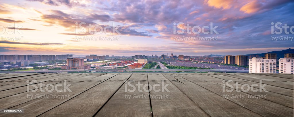 empty wood floor and cityscape of modern city against cloud sky stock photo