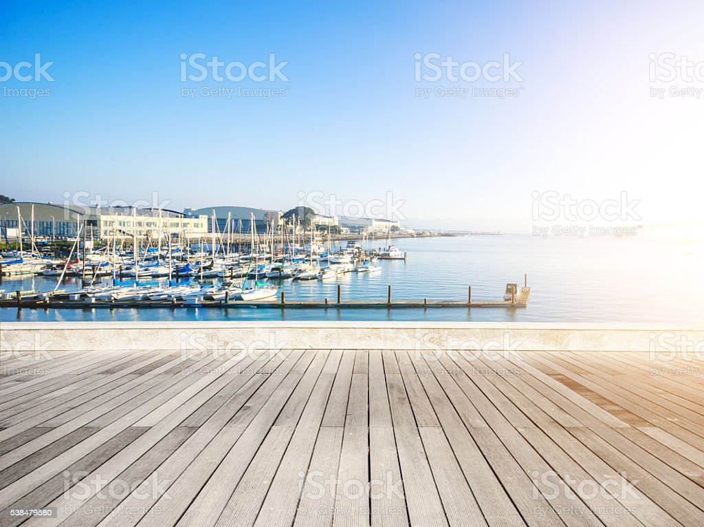 empty wood floor with sail boat in sunny day stock photo