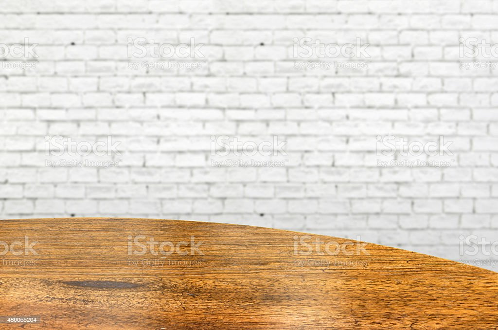 Empty wood round table and white brick wall in background. stock photo