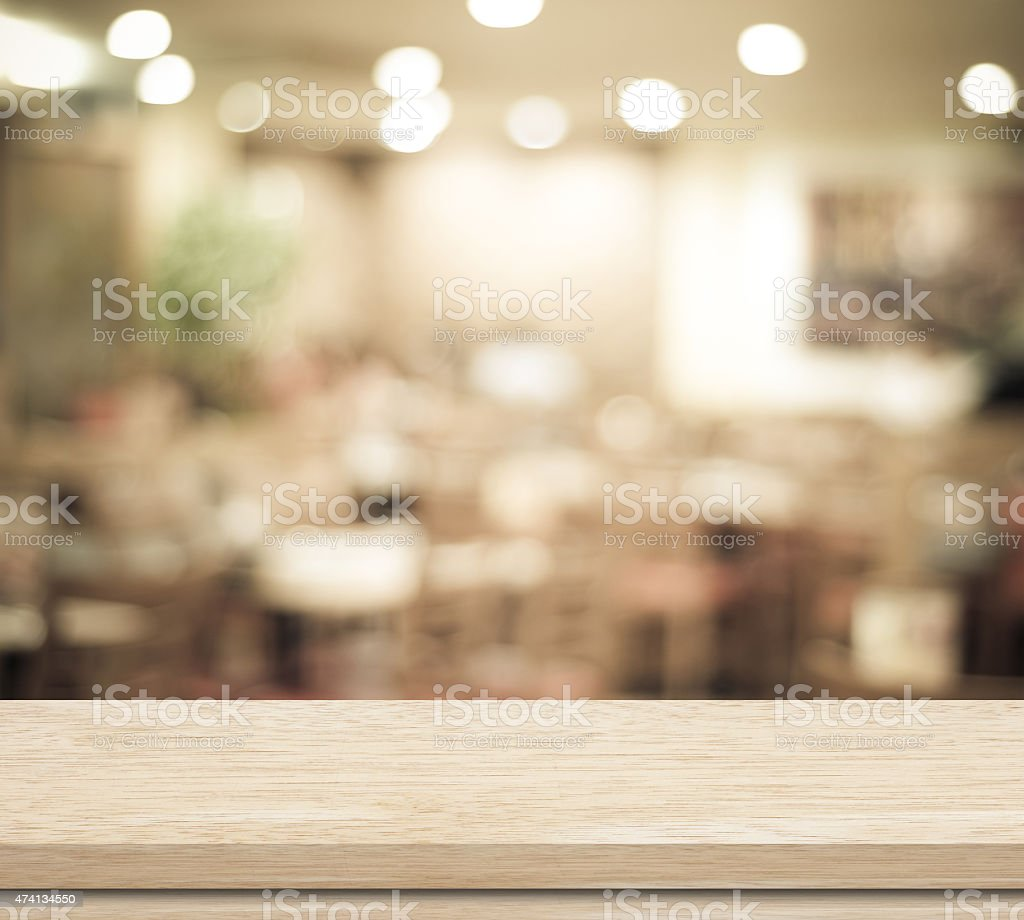 Empty wood table and blurred cafe with bokeh light background stock photo