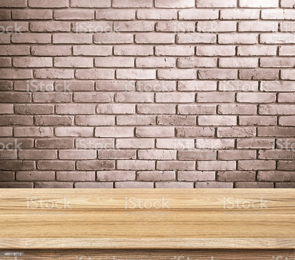 Empty wood table and red brick wall in background stock photo
