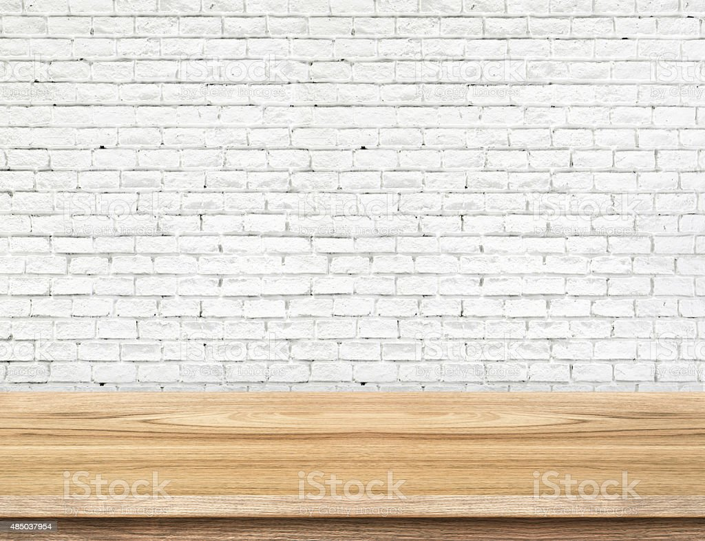 Empty wood table and white brick wall in background stock photo