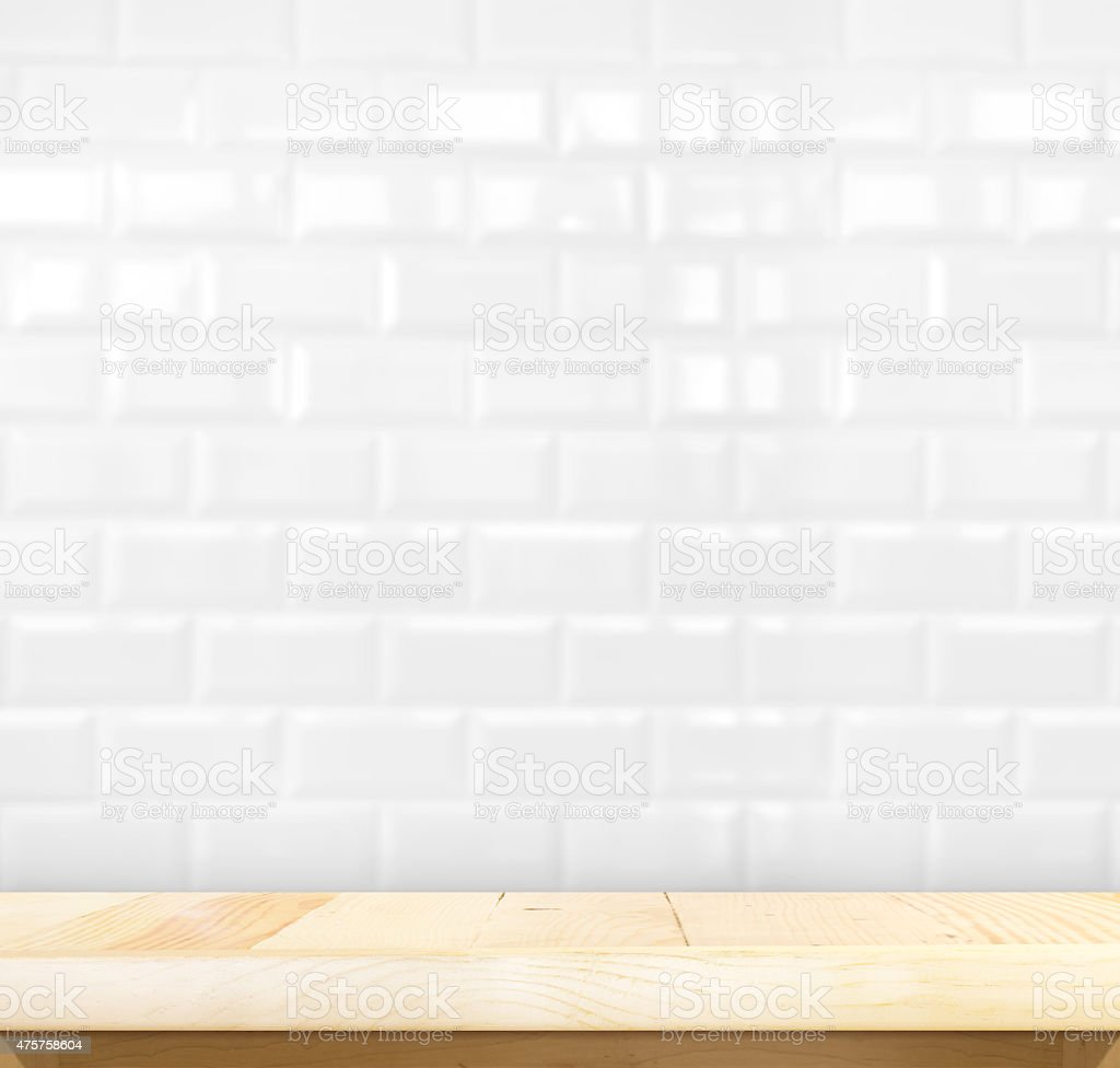 Empty wood table and white ceramic tile wall stock photo