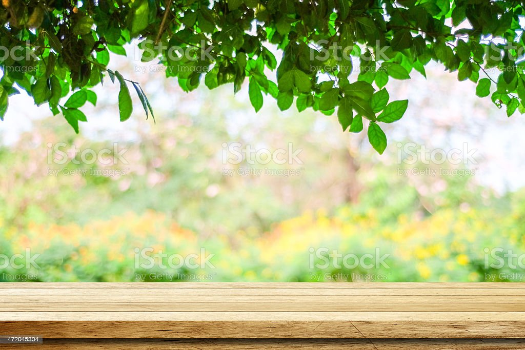 Empty wood table over blurred trees with bokeh background stock photo