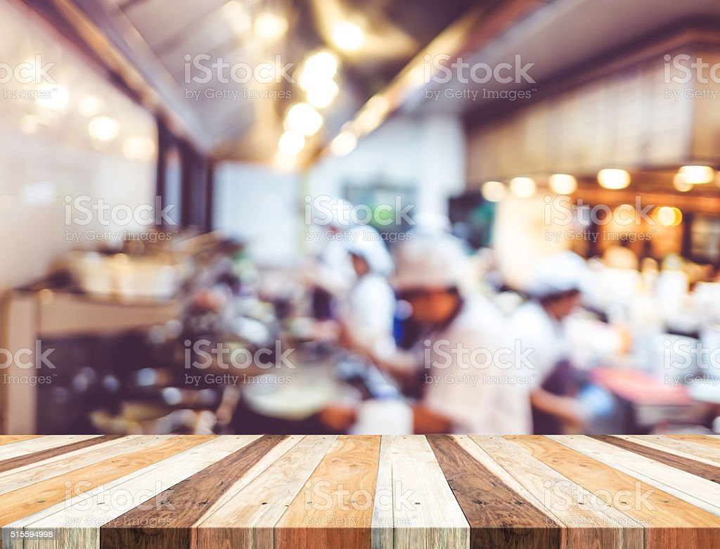 Empty wood table with blur open cooking restaurant background,Mo stock photo