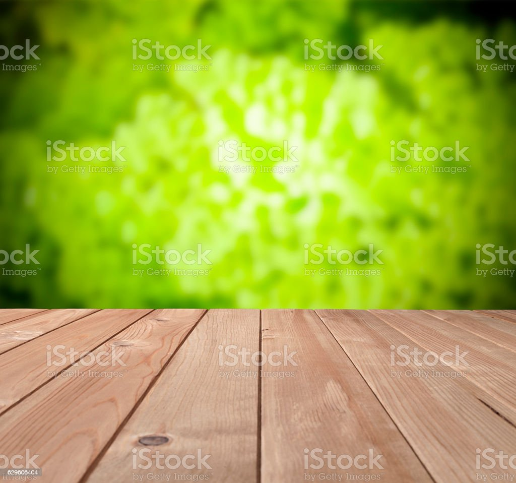 Empty wood table with defocused green foliage at background stock photo