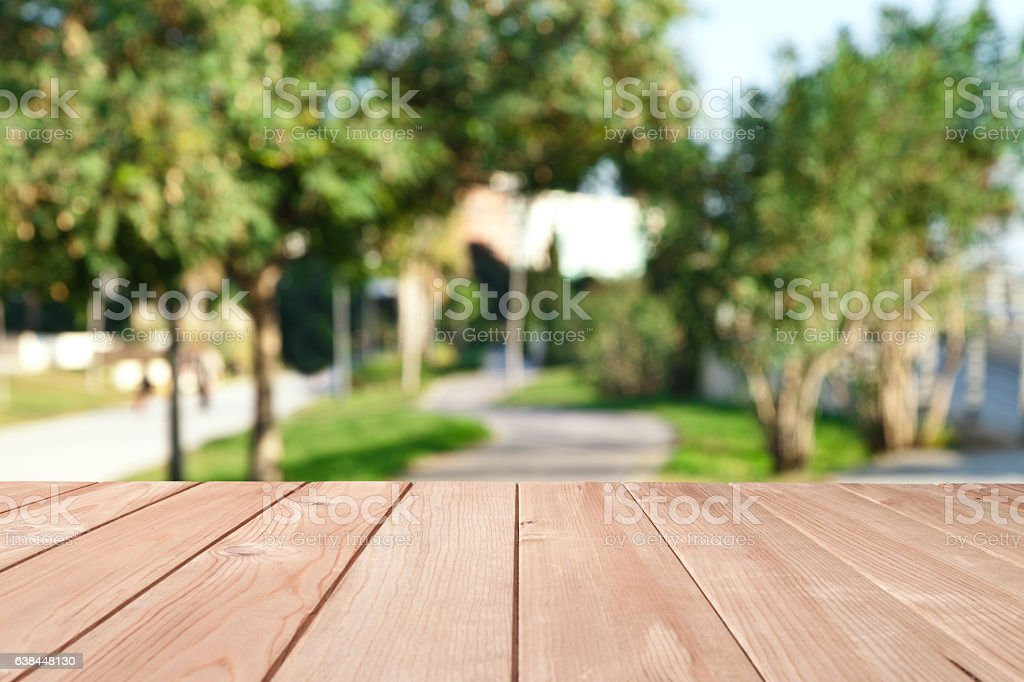 Empty wood table with defocused trees at the park stock photo