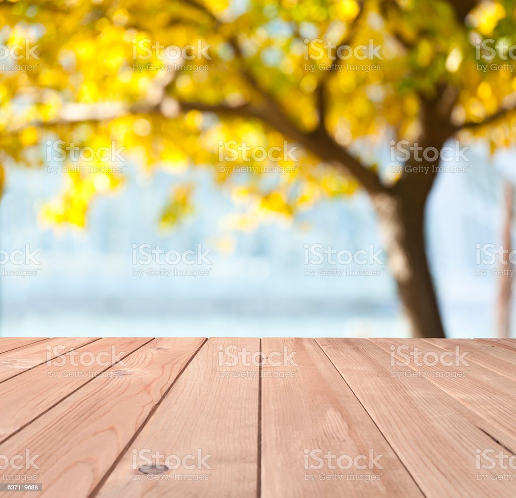 Empty wood table with defocused yellow foliage tree at background stock photo