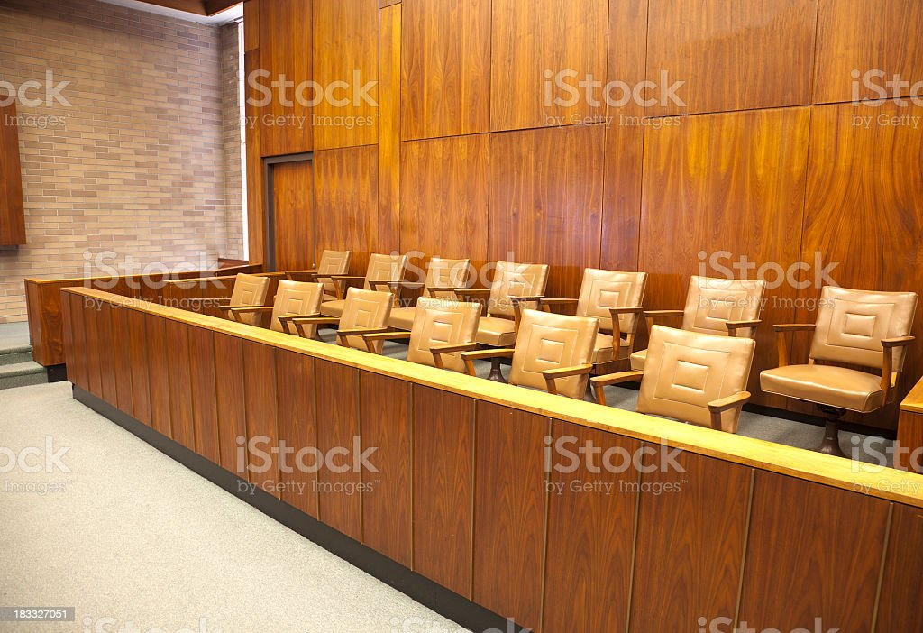 Empty wooden courtroom jury box with beige leather chairs stock photo