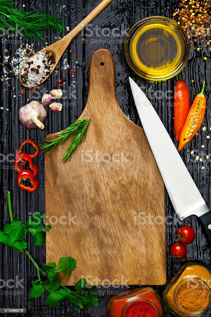 Empty wooden cutting board with cooking ingredients stock photo
