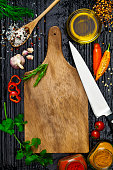 Empty wooden cutting board with cooking ingredients