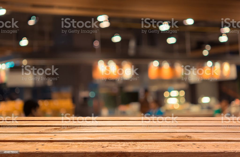 Empty wooden deck table on blurred food court background. stock photo