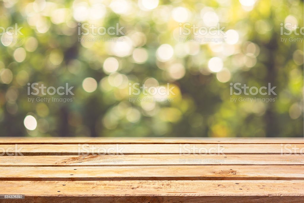 Empty wooden deck table on bokeh natural background stock photo