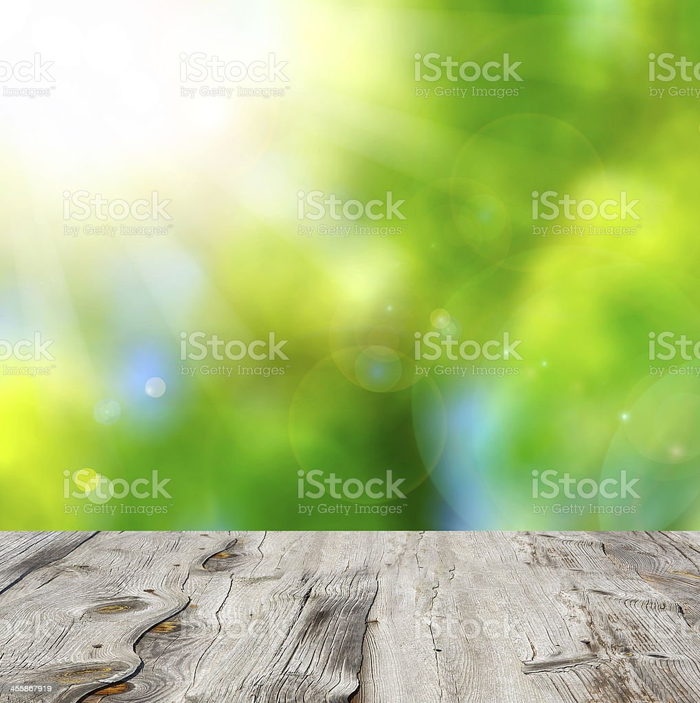 Empty wooden deck table with foliage bokeh background. stock photo