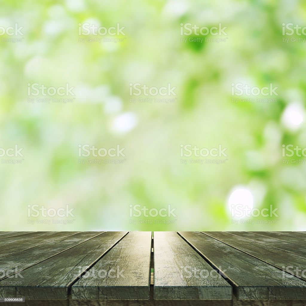 Empty wooden deck table with foliage bokeh background stock photo