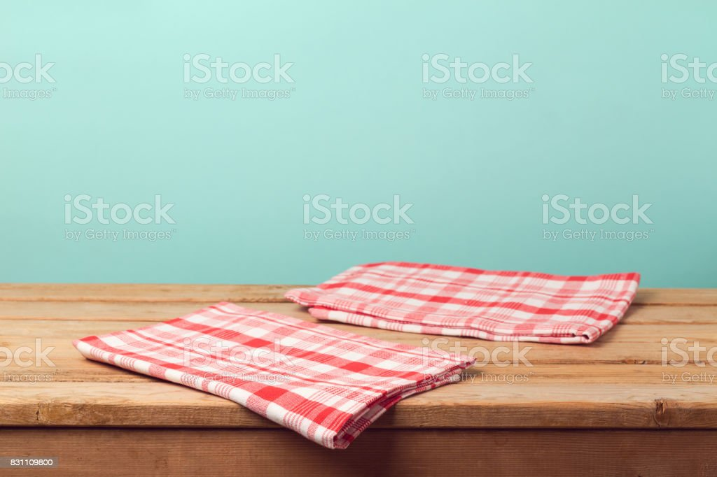 Empty wooden deck table with tablecloth over mint background for...
