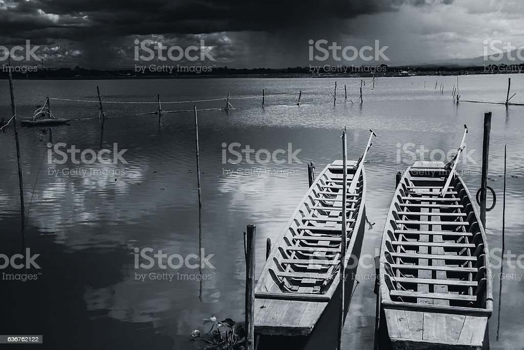 empty wooden fishing boat in rain storm in quiet lake stock photo