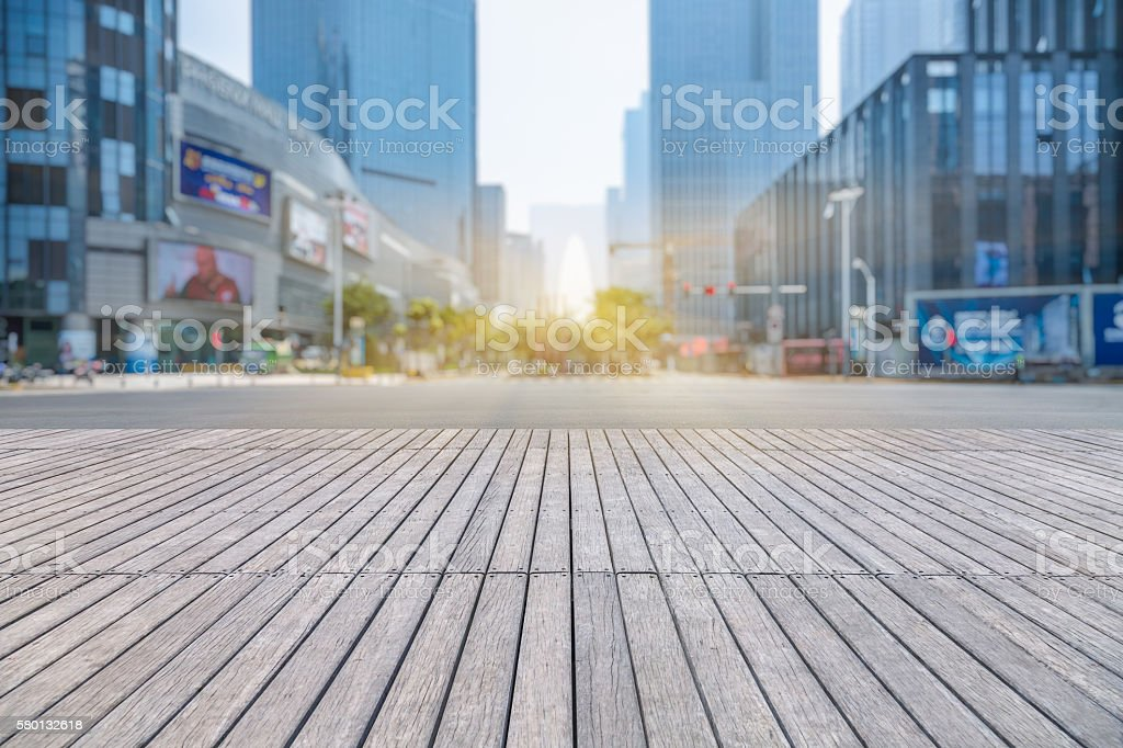 empty wooden floor with modern building in city stock photo